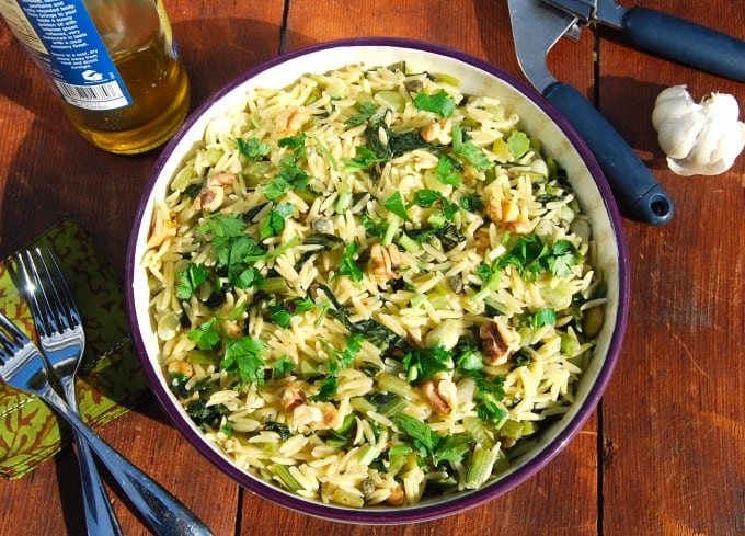Ovrhead shot of Pasta with greens, lima beans, walnuts and capers with forks, olive oil and garlic with a garlic press.