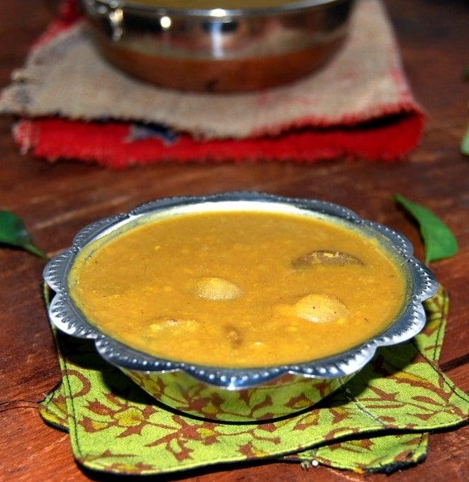Front shot of onion sambar of vengaya sambar in a steel bowl with a karahi in background.