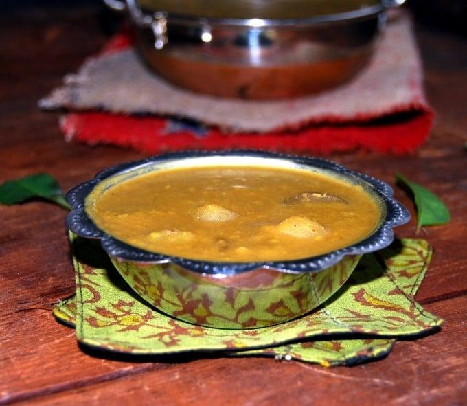 Vengaya Sambar in a steel bowl on a green fabric coaster.