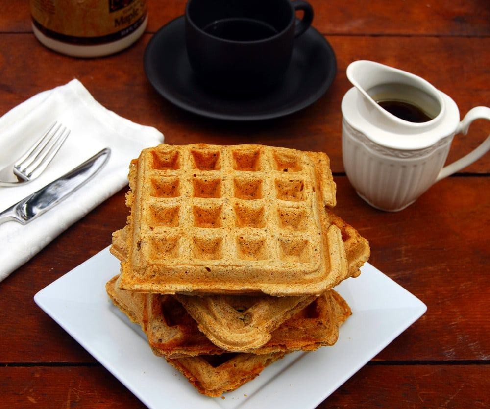 Stack of vegan chia waffles with maple syrup, coffee and fork and knife.