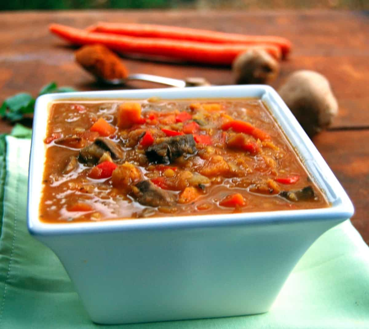 Ethiopian vegetable stew in a bowl with vegetables like carrots and mushrooms in background.