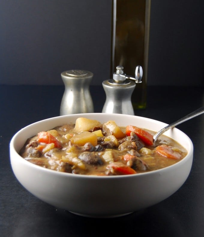 Front shot of a hearty bowl of vegan Irish stew with chunks of soy protein, carrots, celery and potatoes in a white bowl with salt and pepper shakers in the background, and a bottle of oil.