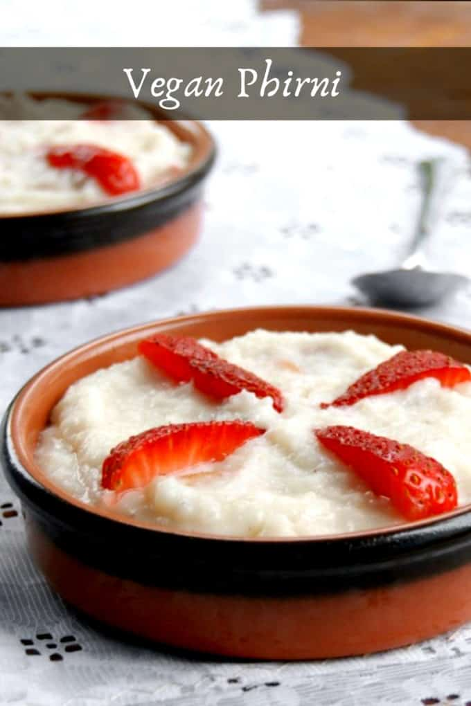 Vegan phirni in a clay bowl with a strawberry garnish on a white lace runner