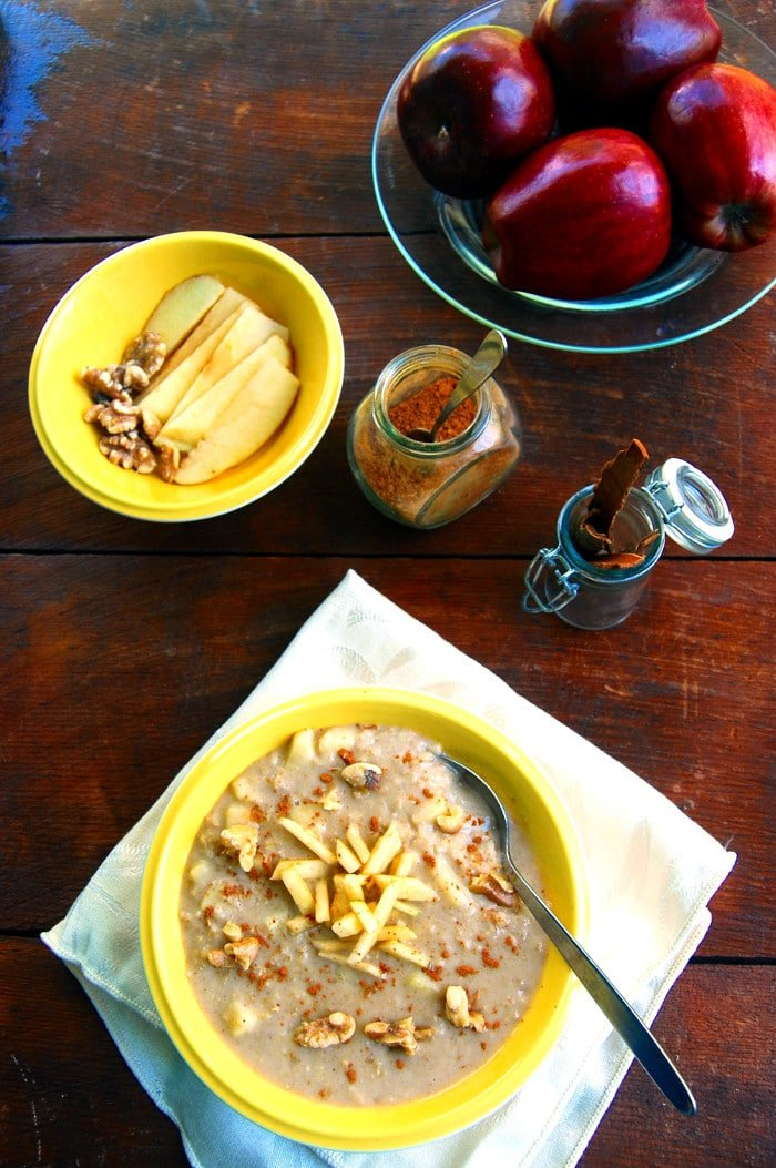 Overhead photo of Apple Cinnamon Oatmeal in bowl with walnuts, apples and cinnamon.