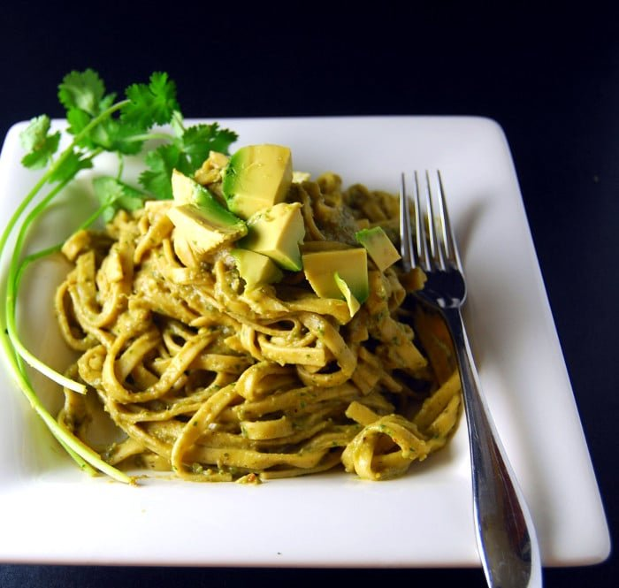 Pasta Avocado in a white square plate with avocado pieces and parsley.