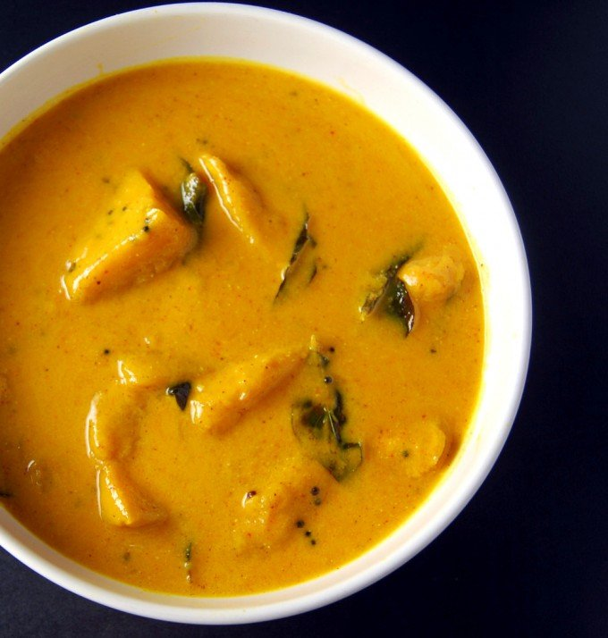 Photo of Vegan Mango Curry in a white bowl with chunks of mango, mustard seeds and curry leaves.