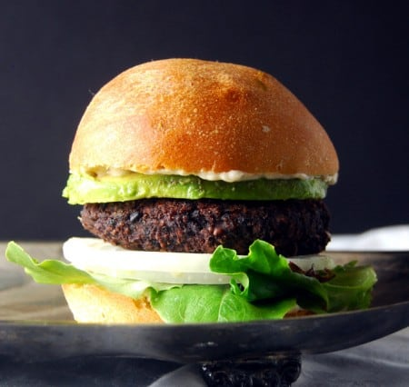 A Black Bean Black Rice Veggie Burger with greens, avocado and onion on a silver tray.