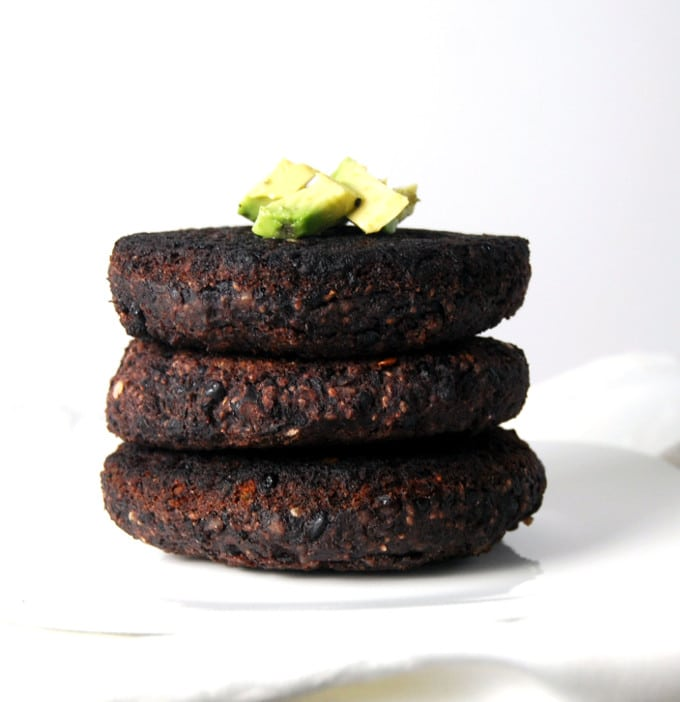 A stack of Black Bean Black Rice Veggie Burger patties topped with avocado pieces.