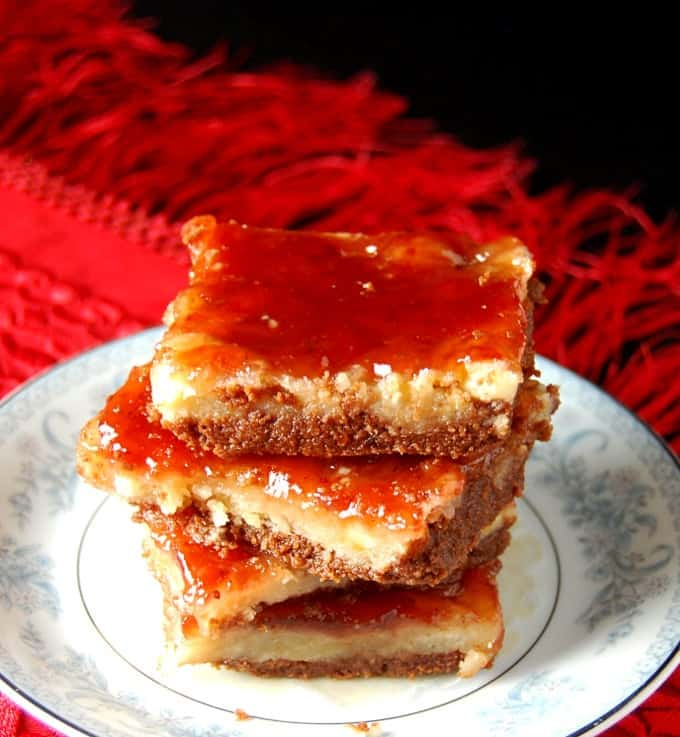 Front photo of Chocolate Strawberry Shortbread bars stacked on a blue and white ceramic plate against a red tablecloth.