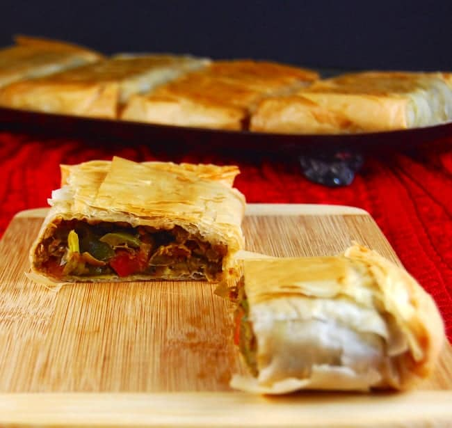 A section of a Curried Lentil Hand Pie on a wooden chopping board with more hand pies sitting in the background | holycowvegan.net