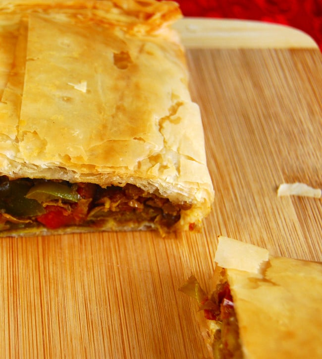 A cross section of a Curried Lentil Hand Pie with a filling of lentils and vegetables, sitting on a wooden chopping board | holycowvegan.net