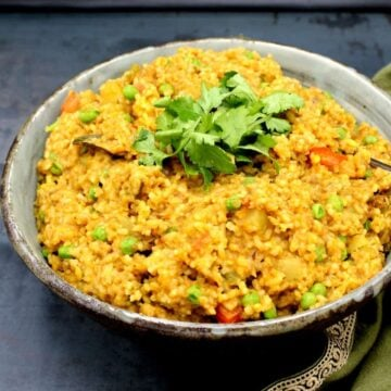 Masala Khichdi in a large earthenware bowl with cilantro.