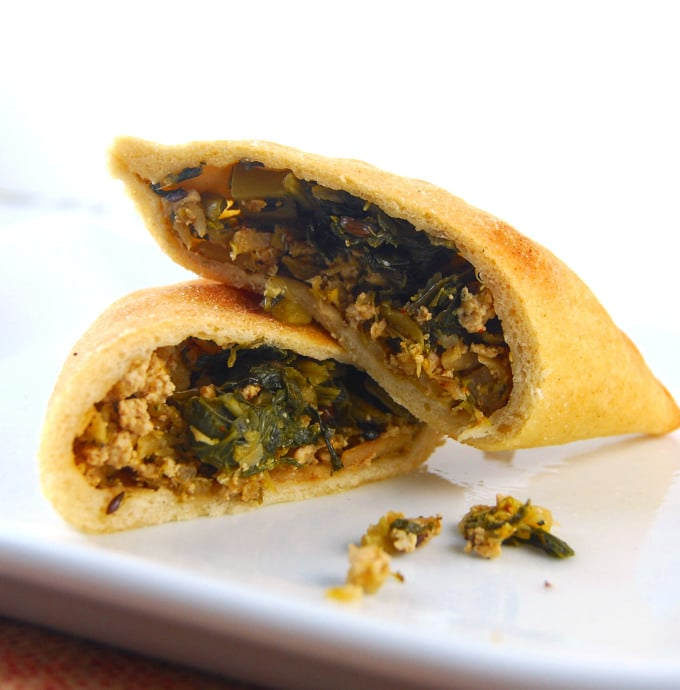 Cross section of a pita packet with broccoli, spinach and tofu filling on a white plate.
