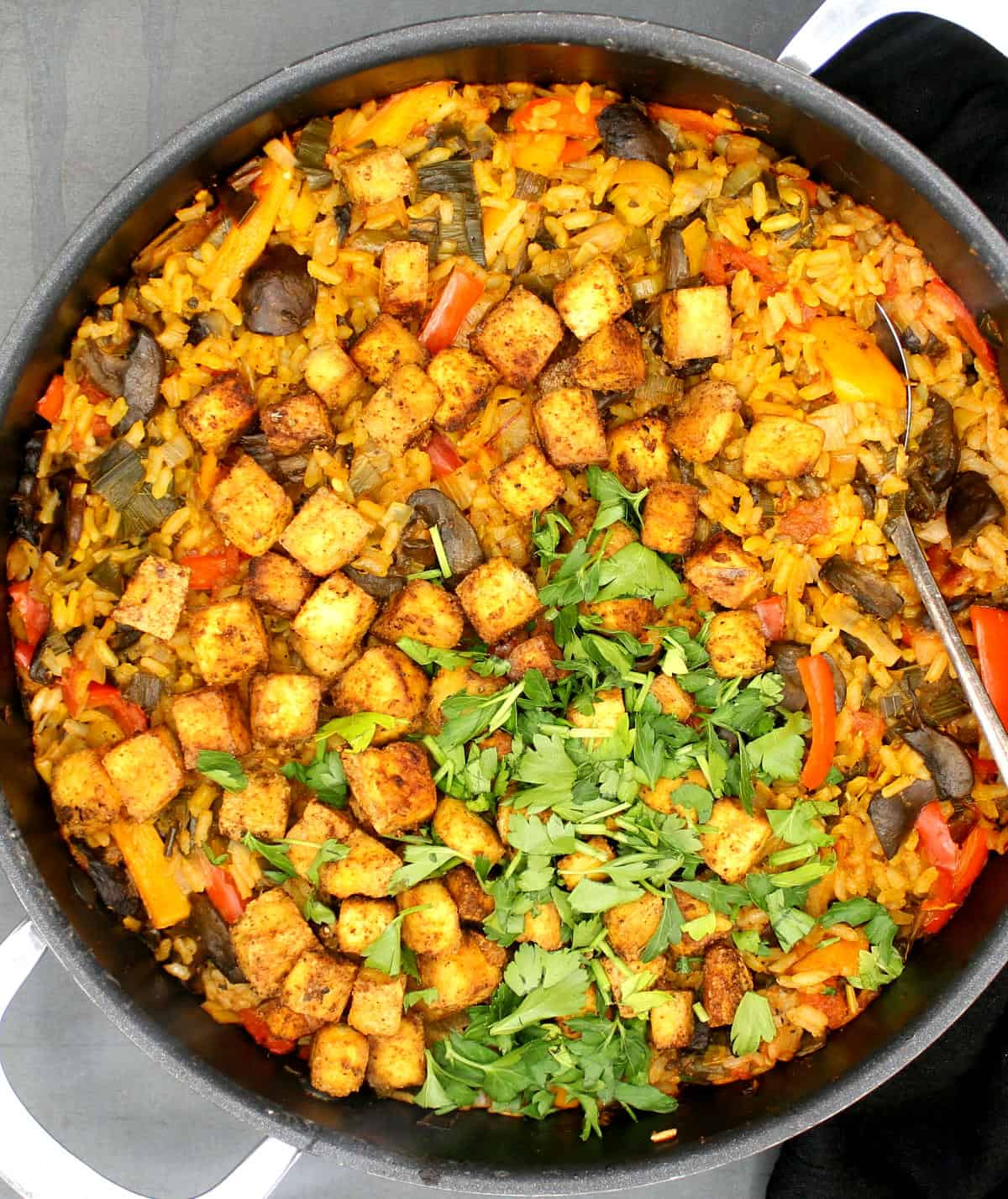 Overhead closeup of a skillet with vegan paella with a spoon in it.