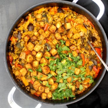 "Overhead shot of a vegan paella cooked in a wide skillet with ""seafood"" tofu and parsley"