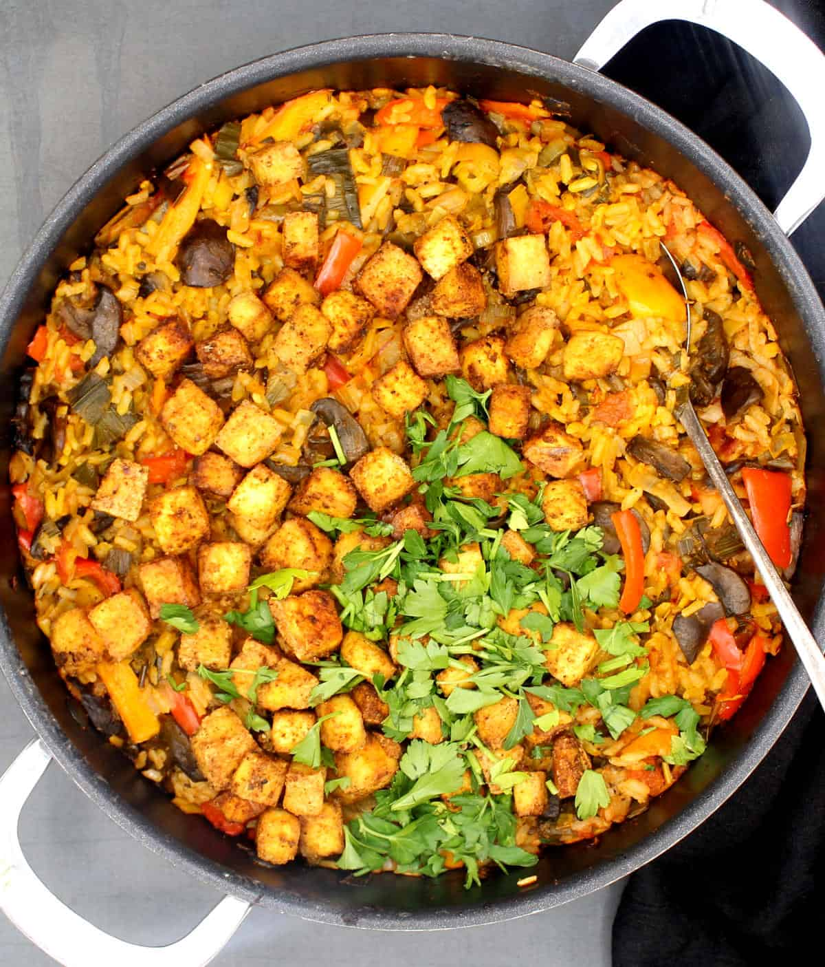 A skillet containing a just-cooked vegetable paella with tofu, veggies like bell peppers and mushrooms, and a parsley garnish.