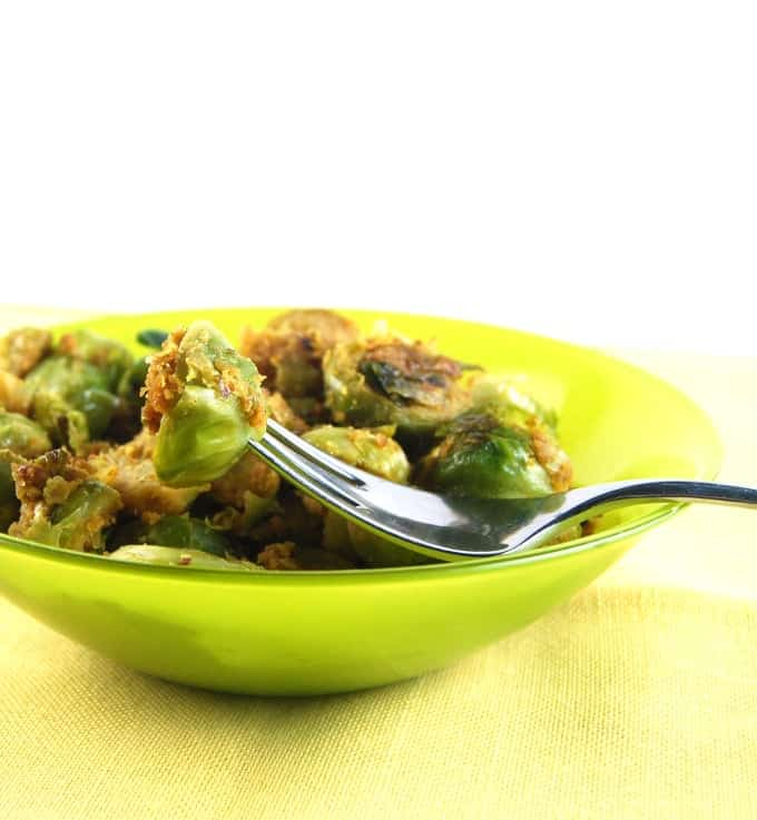 Pan-roasted brussels sprouts in a green bowl with fork