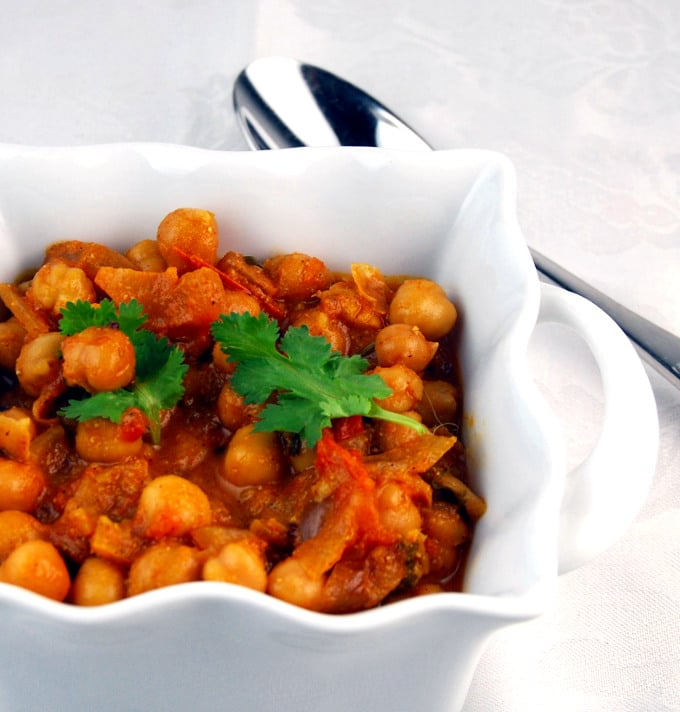 A closeup of south Indian chickpea curry with cilantro in a square white ceramic bowl with a steel spoon on the side