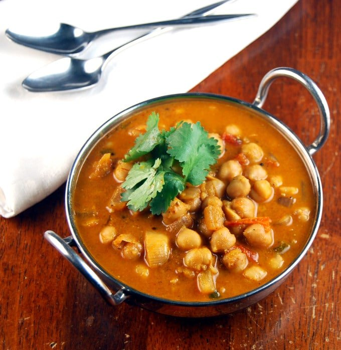 A top view of steel kadhai bowl with chickpea curry garnished with cilantro with two spoons on a white napkin next to it all on a wooden table