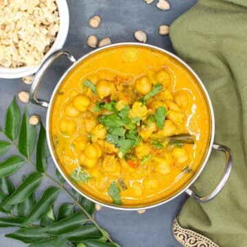 Chickpea Curry in karahi bowl with brown rice and chickpeas and curry leaves around it.