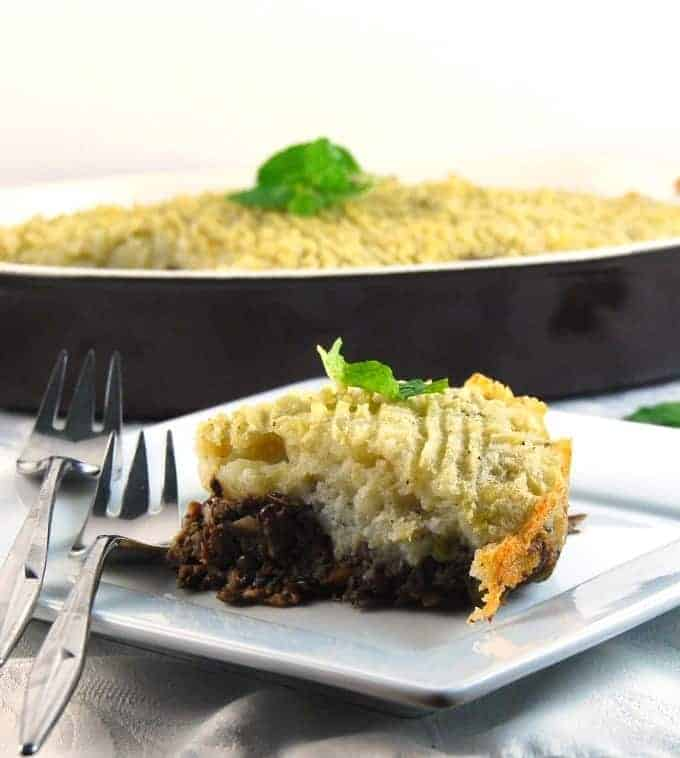 A slice of savory vegan lentil shepherd's pie with a base of lentils and mushrooms topped with a creamy layer of potatoes on a white plate with two forks