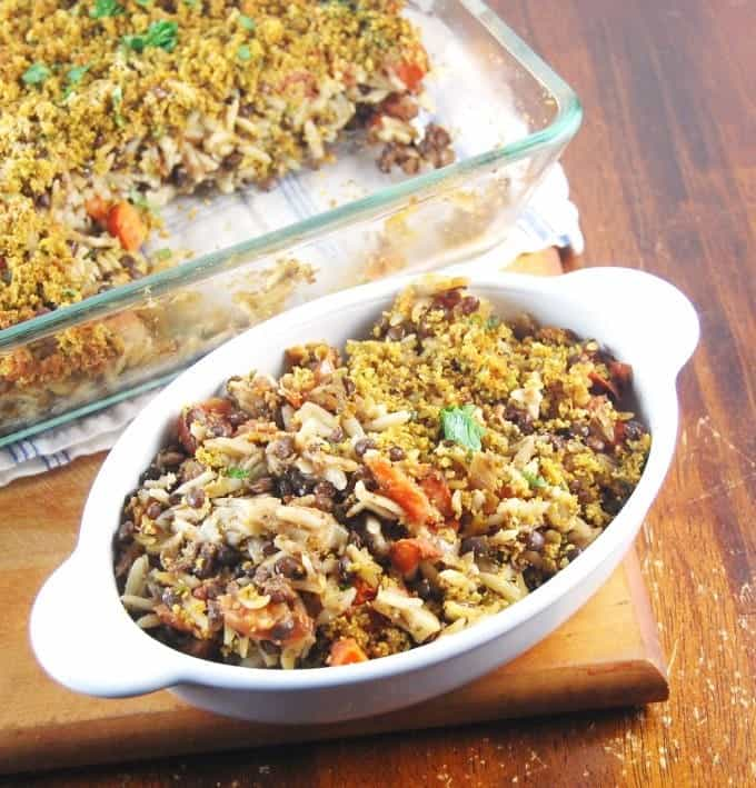 Photo of vegan lentil orzo bake with cheesy crust in a baking pan and served in an oval ceramic bowl.