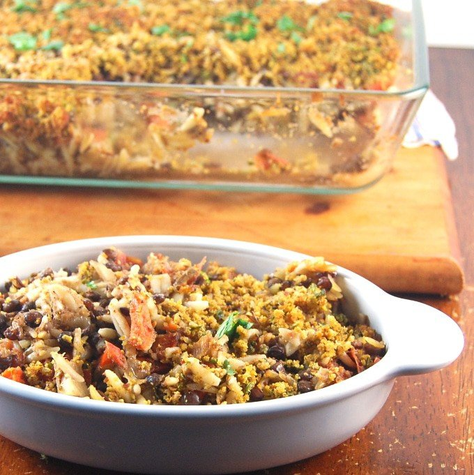 Lentil-Orzo Bake in an oval ceramic dish with the baking pan with more behind.