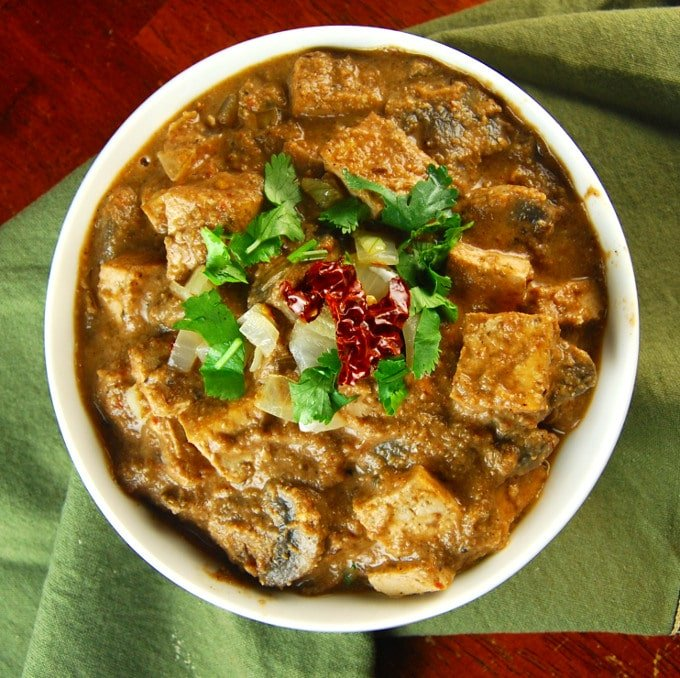 A bowl of Tofu Paneer Do Pyaza with cilantro and roti near it.