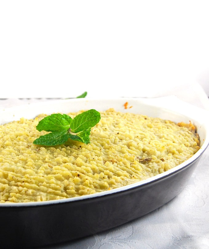 A front view of vegan Irish shepherd's pie in a brown baking dish topped with a sprig of mint
