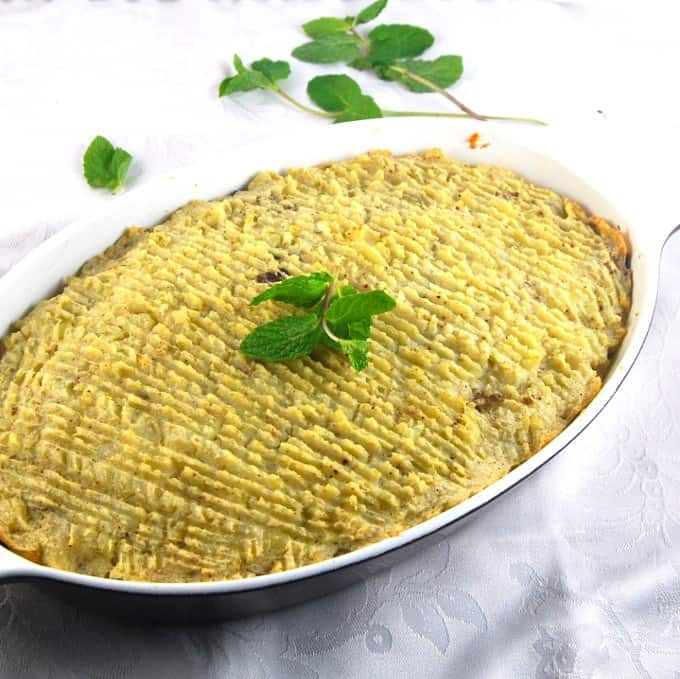 A baking dish of vegan shepherd's pie with a potato crust and sprigs of mint