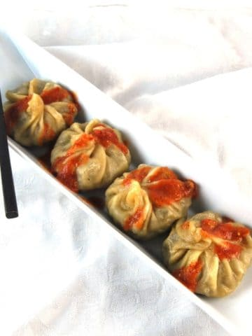 Vegan Momos in a white dish with chopsticks and red sauce