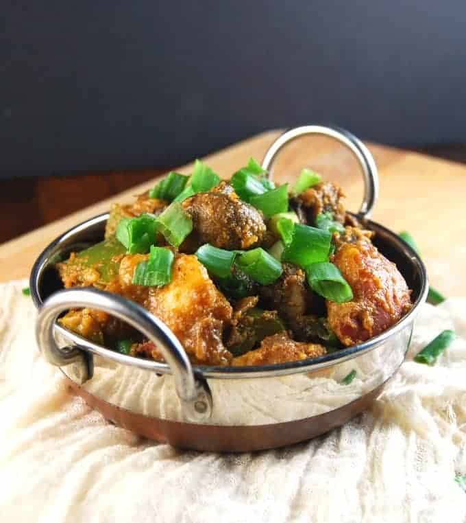 Vegetable Balti in a karahi bowl with potatoes, mushrooms, onions, peppers and potatoes with a scallion garnish.