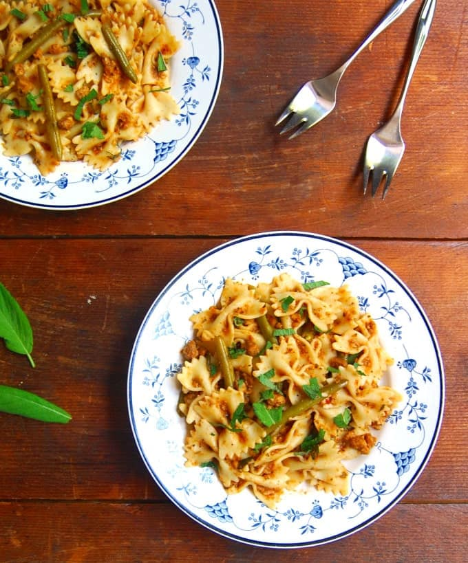 Bowtie Pasta in a Light Bolognese sauce in two blue and white plates with forks and sage scattered around.