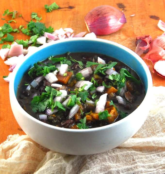 Fat-free Cuban Black Bean Stew served in a blue and white bowl with shallots and cilantro.