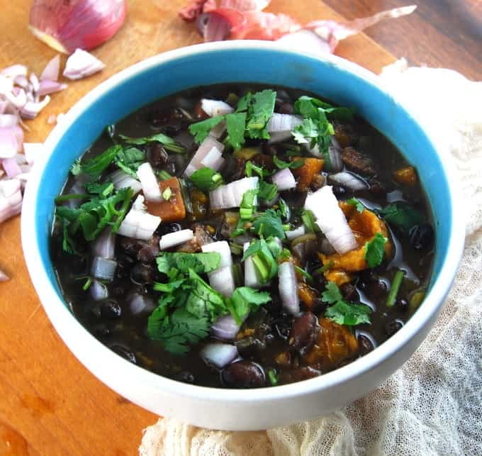 Photo of Oil-free Vegan Cuban Black Bean Stew cooked in a Crockpot and served in a bowl.