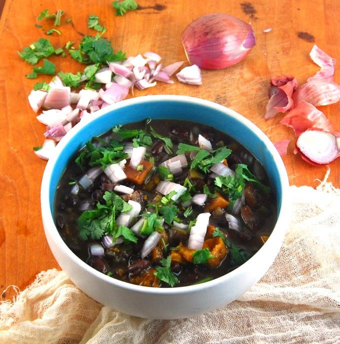 Fat-free Cuban Black Bean Stew in a bowl with shallots and cilantro.