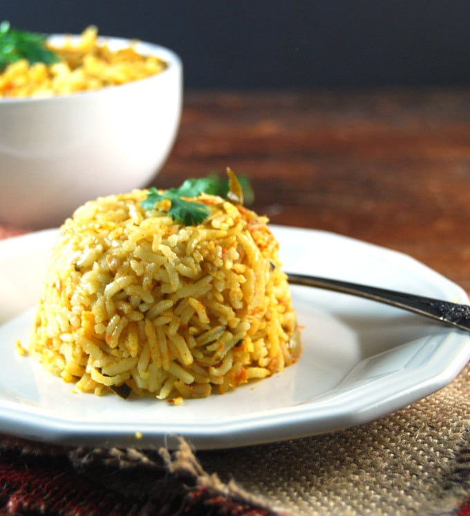 Methi Tomato Rice, an easy and tasty pilaf, served in a white plate with fork.