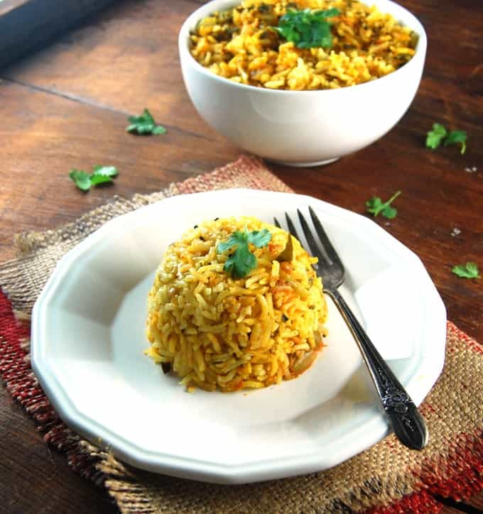 Methi Tomato Rice served in a white plate an d a bowl witha  fork.