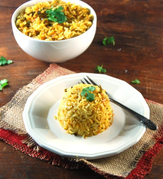 Methi Tomato Rice in a white plate with fork.