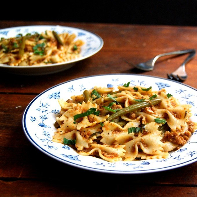 Bowtie Pasta in a Light Bolognese in blue and white plates with forks on a wooden background.