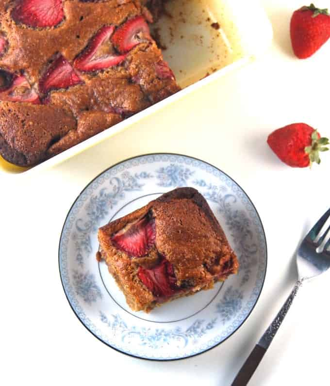 Photo of a slice of vegan strawberry bread with a baking pan with cake behind it and a few scattered strawberries.