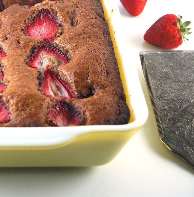 Photo of a yellow baking dish with vegan Strawberry Bread with silver serving spoon and strawberries.