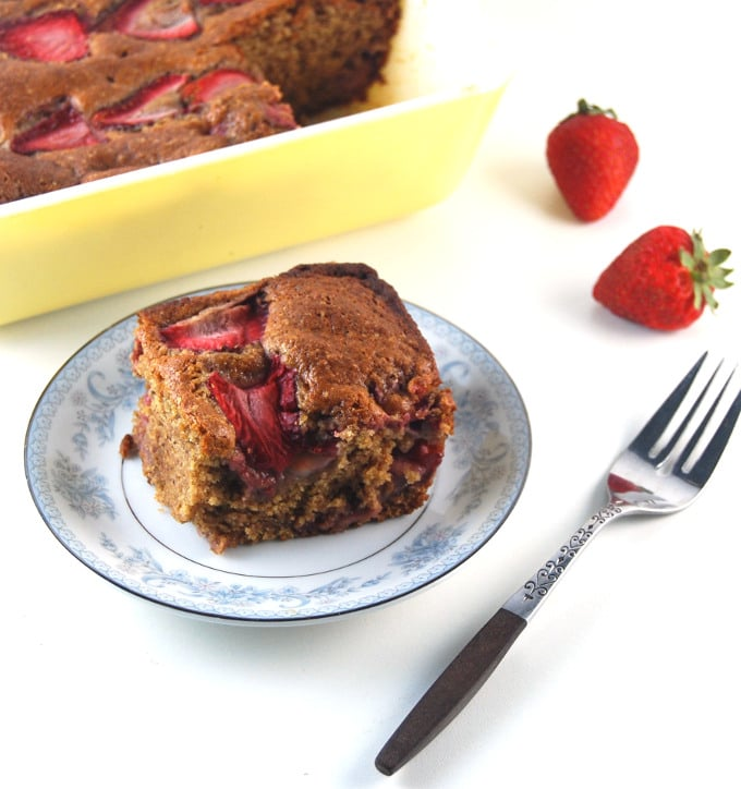 Photo of a slice of vegan strawberry bread in a blue and white ceramic dish with a yellow baking dish in background and strawberries and fork next to it.