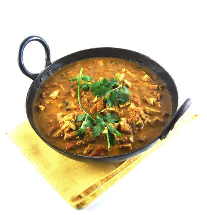 "Tofu Egg Curry, an Indian style curry with vegan ""eggs"" in a black karahi with cilantro garnish."