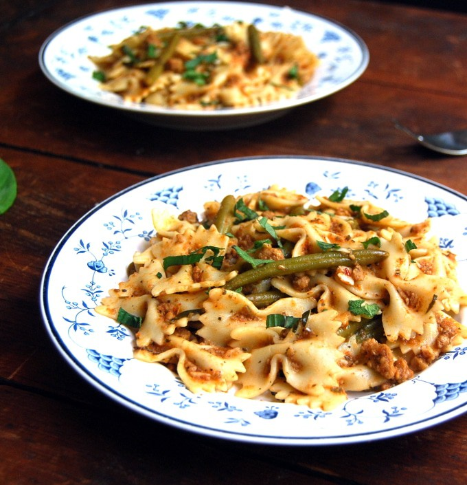 Bowtie Pasta in a Light Bolognese in plates on wooden table.
