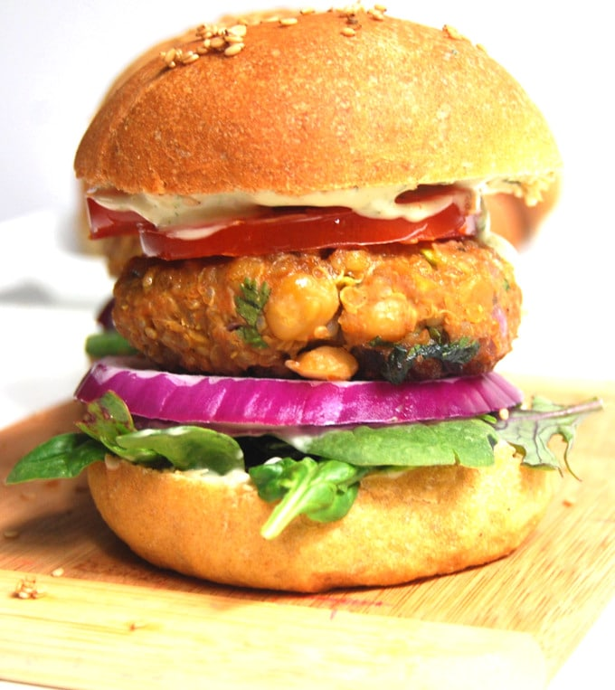 Closeup of a chana masala burger with greens, onions and tomatoes in a whole wheat bun.