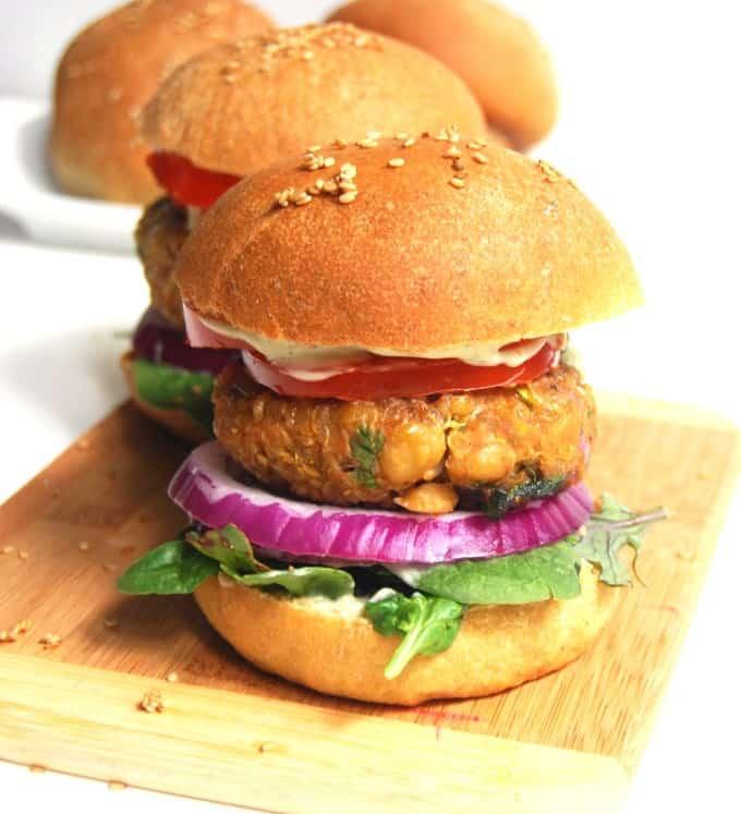 Chana masala burgers on a chopping board.