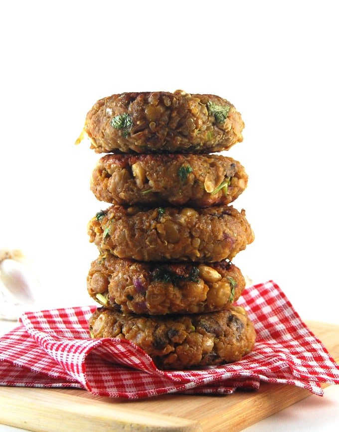 A stack of chana masala burger patties stacked on a red and white napkin.