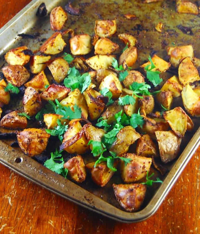 Closeup of Golden Roasted Curry Mustard Potatoes on baking sheet.