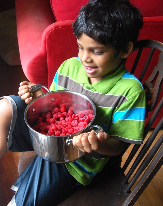 My son Jay holding up a pot filled with raspberries.